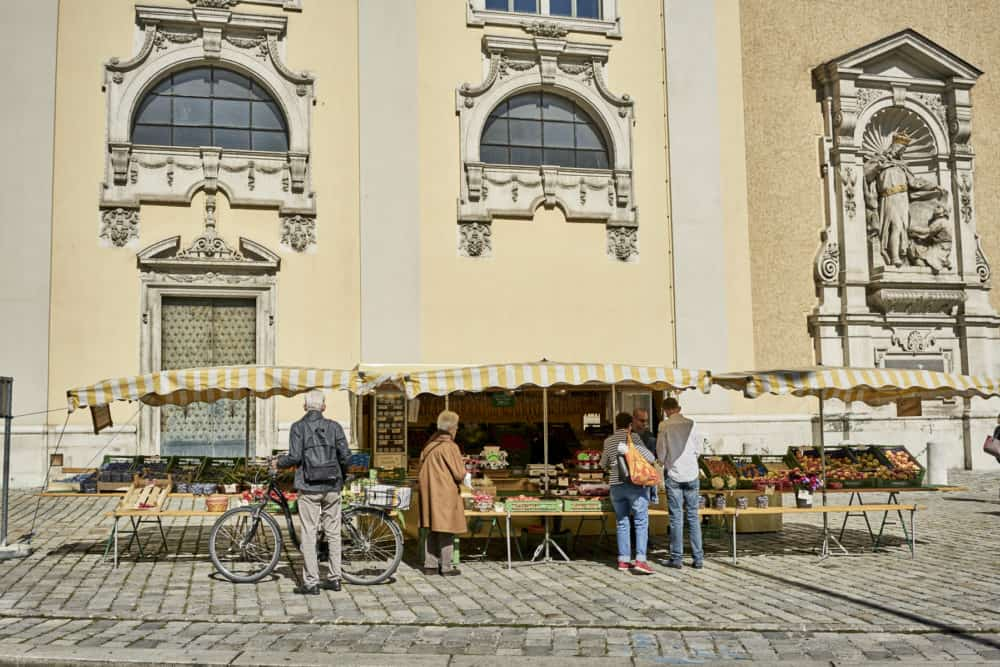 Men and women buying goods from a small produce stand with yellow and white striped awnings in Vienna. It is on a cobble-stoned street with a pale yellow Beaux Arts style building in the background.