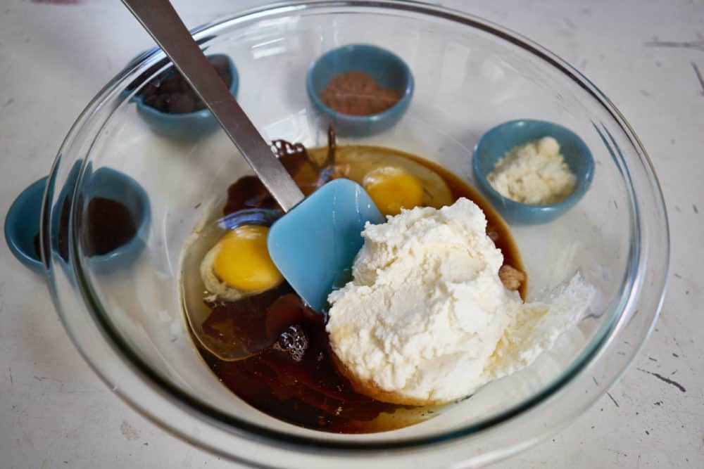 A glass bowl with a blue spatula containing brownie ingredients: ricotta cheese, eggs, vanilla and maple syrup. Small blue bowls with chocolate chips,cocoa, and almond flour are in the background.