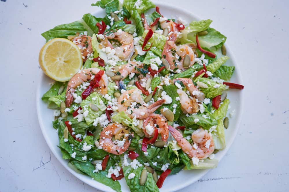 Shrimp salad with romaine and cherry peppers on a white plate.