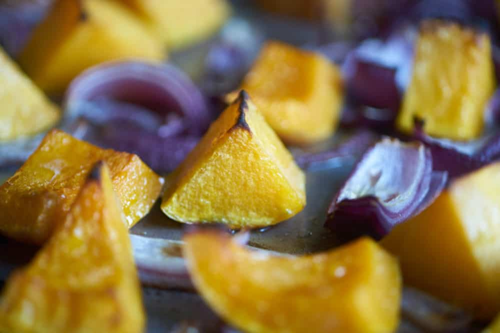 Roasted butternut squash and red onions on a silver sheet pan.