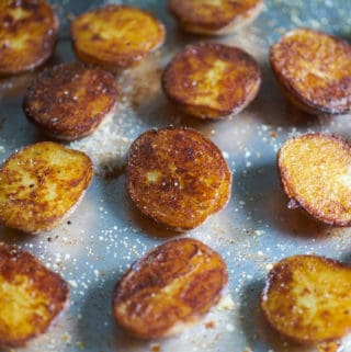 Crispy roasted potatoes seasoned with salt and pepper on a sheet tray with a silver spatula.