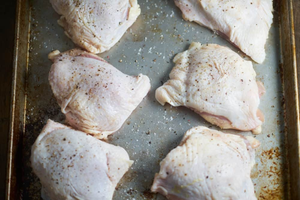 Raw chicken thighs seasoned with salt and pepper on a sheet pan.