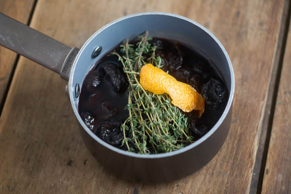 Dried plums soaking in beaujolais with fresh thyme and orange peel in a small saucepan, to be made into sauce for chicken in red wine with dried plums.