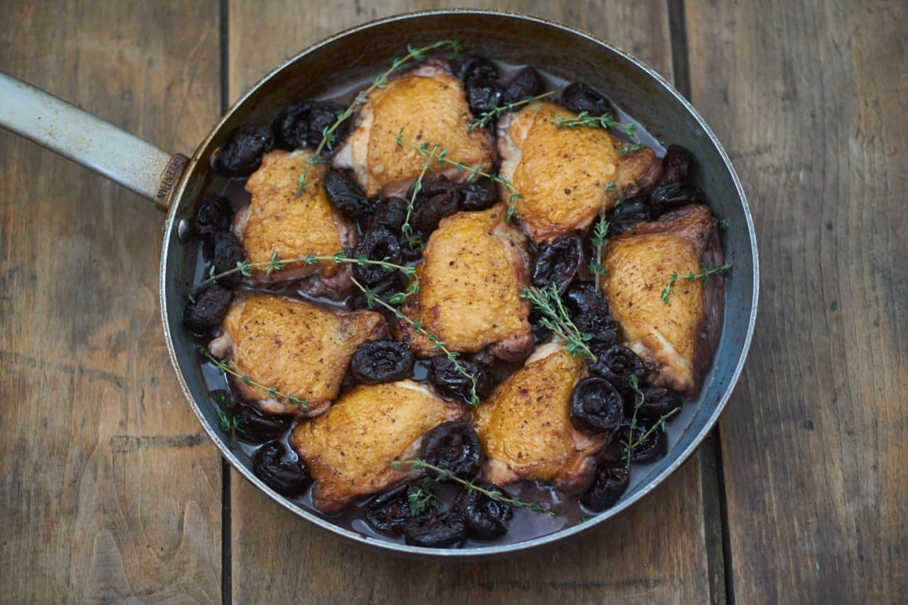 Chicken thighs in red wine with dried plums topped with fresh thyme in a skillet on a wooden surface.