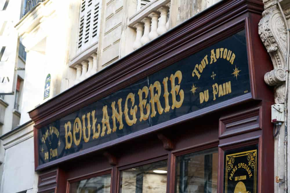 Exterior sign of a bakery in the Marais neighborhood in Paris. The sign is black with gold lettering and reads: Boulangerie Tout Autour du Pain.