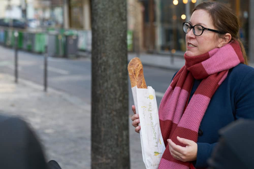 A tour guide from Paris by Mouth stands on the sidewalk in the Marais neighborhood in Paris. She holds a baguette, she is wearing a blue coat and a red and pink striped scarf.