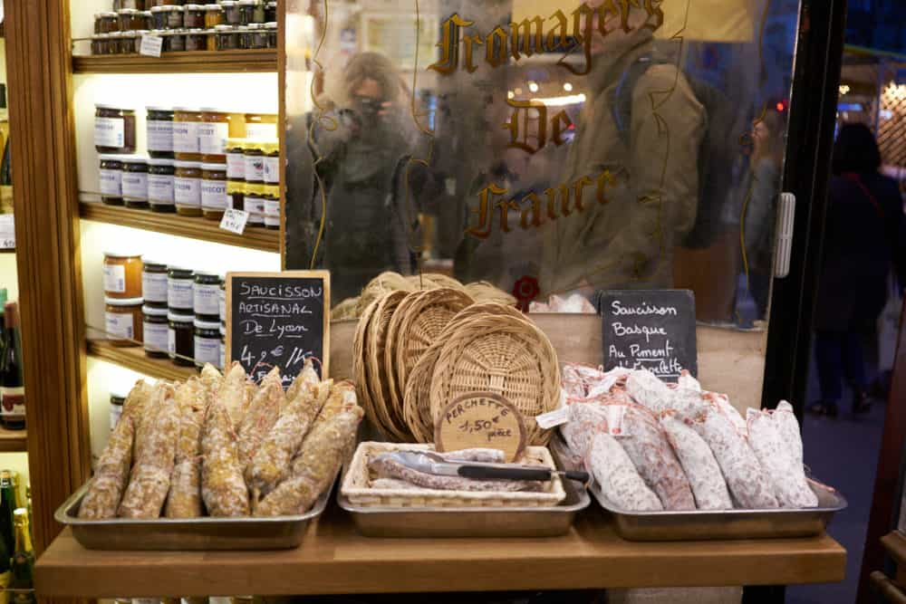 Trays of French charcuterie and woven baskets sit on a small wooden table at the entrance to a cheese shop in the Marais neighborhood of Paris. Shelves of jams and other jarred products are seen in the background.