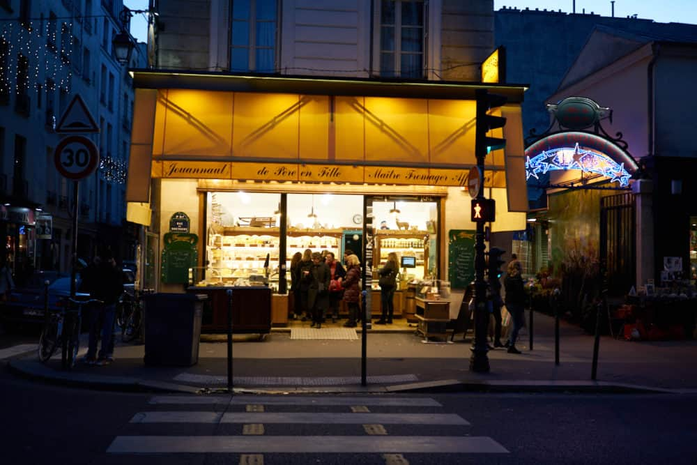 The exterior of Fromagerie Jouannault, a cheese shop in the Marais neighborhood of Paris. The awnings are yellow, a cross walk is in the foreground.