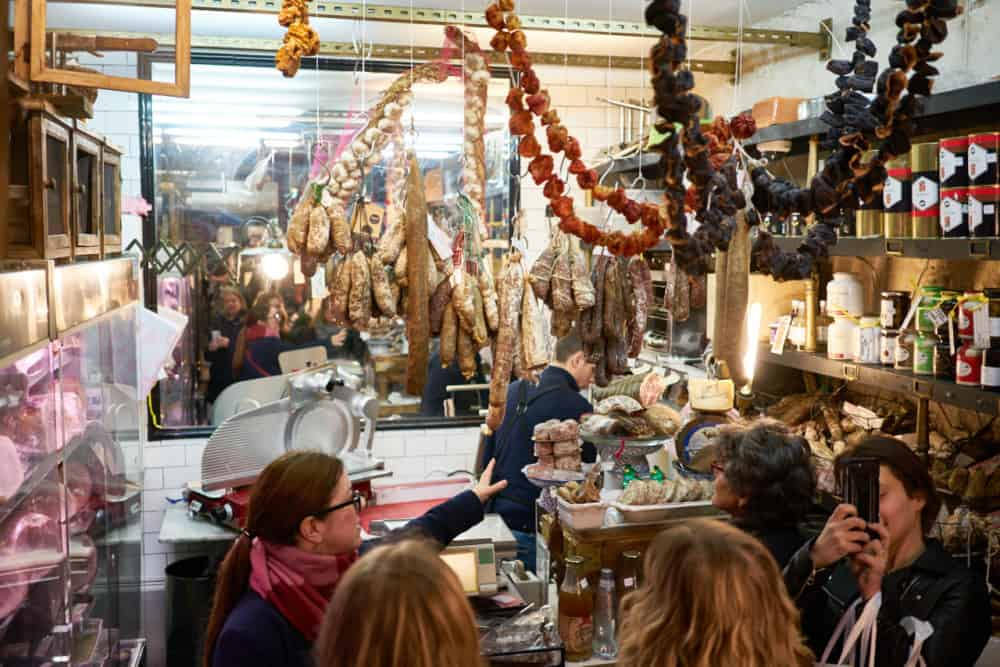 The interior of Caractère de Cochon, a charcuterie in the Marais neighborhood in Paris. Sausages and dried peppers are hanging from the ceiling. A tour guide and tour group is in front of the counter as a man slices charcuterie behind it.