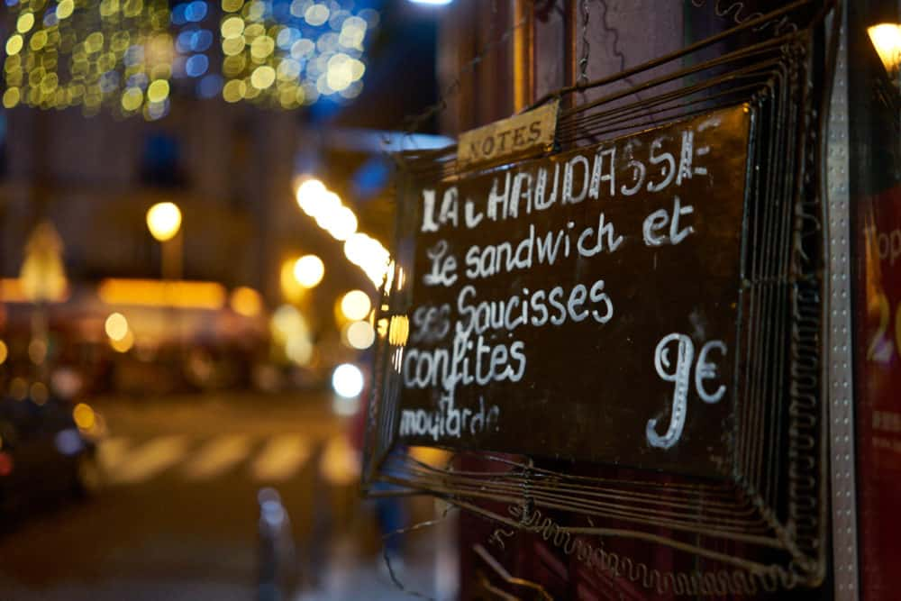 A sign on a charcuterie shop doorway in Paris in the Marais neighborhood with the special of the day written on it. It reads: La Chaudasse. Le sandwich et ses saucisses confites, moutarde 9 euros.