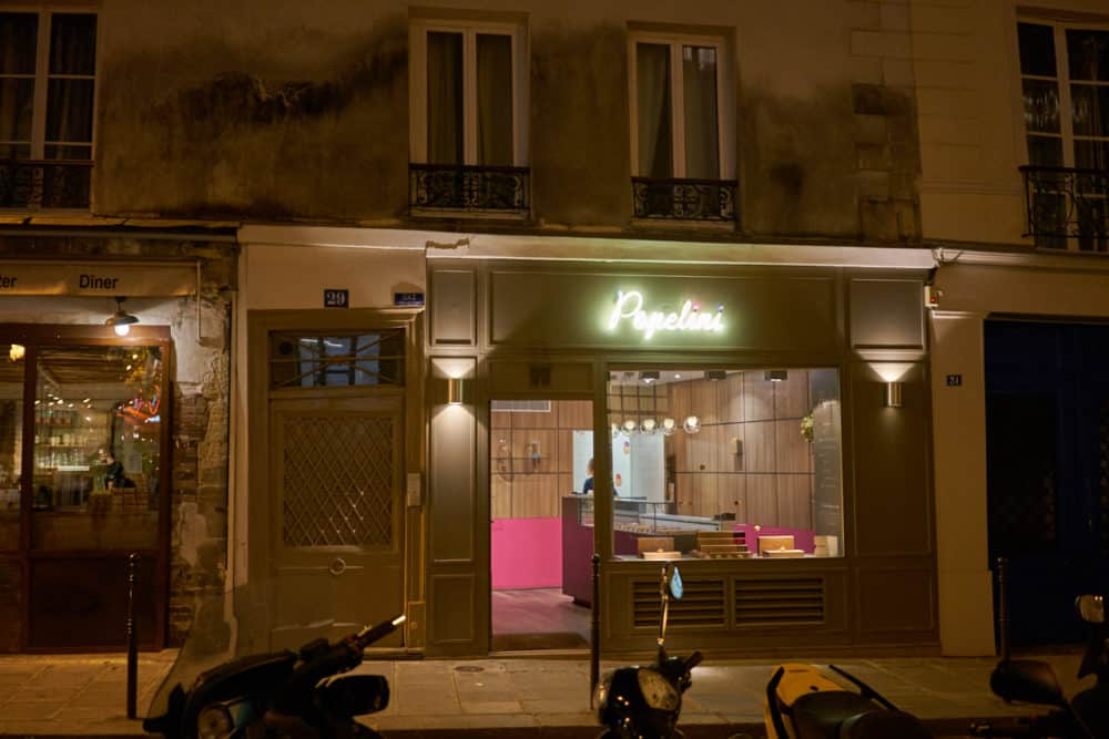 The exterior of Popelini in the Marais neighborhood of Paris. The shop sells small cream puffs in a variety of flavors. A white neon sign that says Popelini is lit over the entrance.