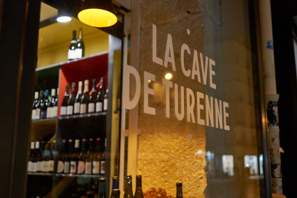 The window of La Cave de Turenne, a wine shop in Paris in the Marais neighborhood. The name of the store is written on the glass and wine bottles can be seen on the shelves inside the store.
