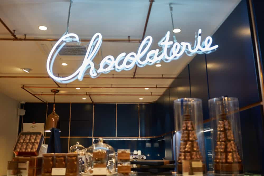 """Inside La Chocolaterie Cyril Lignac in Paris. A white neon sign that says """"Chocolaterie"""" hangs over a counter with pastries and chocolate. The interior walls are dark blue."""