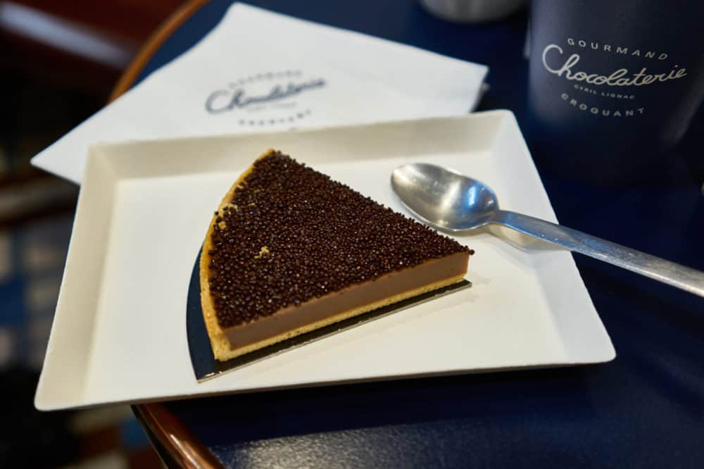 A chocolate hazelnut tart on a white plate sits on a blue table at chocolaterie Cyril Lignac in Paris. A spoon is resting on a plate and a napkin with the chocolaterie's logo is above the plate.