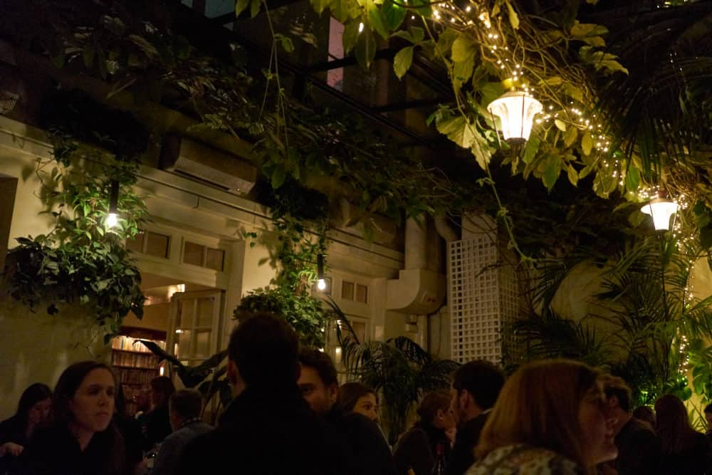 The dining room at Hotel Amour in Paris. The glass walls and ceiling are lined with plants, greenery and strings of lights. People are sitting at bistro tables throughout the dimly lit room.