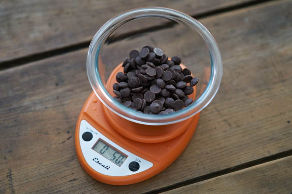 An orange kitchen scale weighs a glass bowl filled with dark chocolate chips