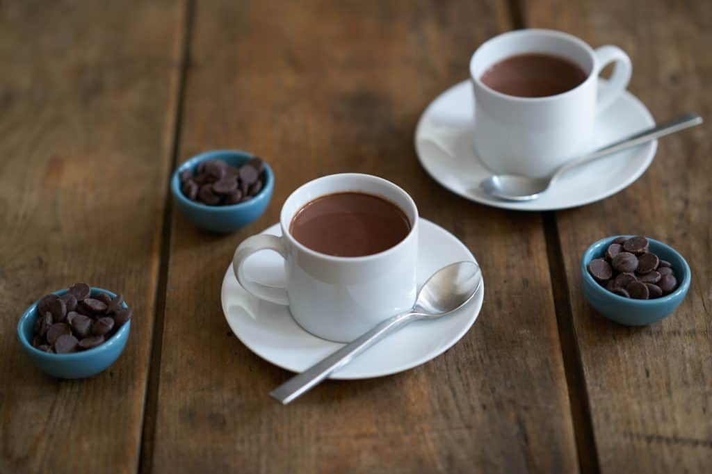 Two white cups filled with French-style hot chocolate, or chocolate chaud, surrounded by three small blue bowls filled with dark chocolate chips.
