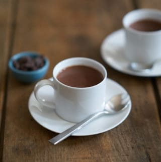 Two white cups filled with French-style hot chocolate, or chocolate chaud, surrounded by three small blue bowls filled with dark chocolate chips