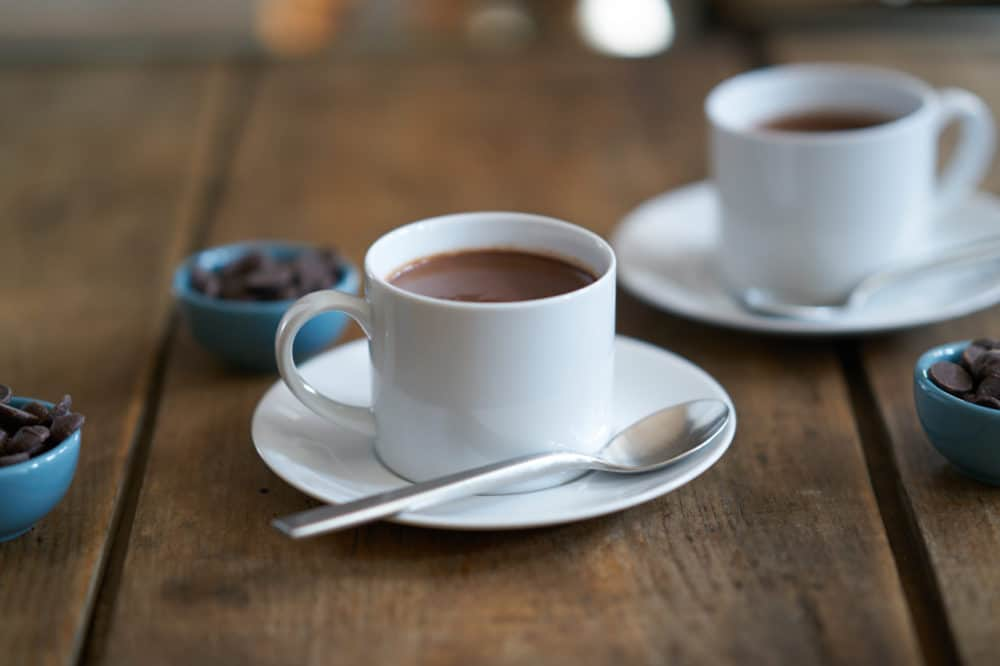 Two white cups filled with French-style hot chocolate, or chocolat chaud, surrounded by three small blue bowls filled with dark chocolate chips
