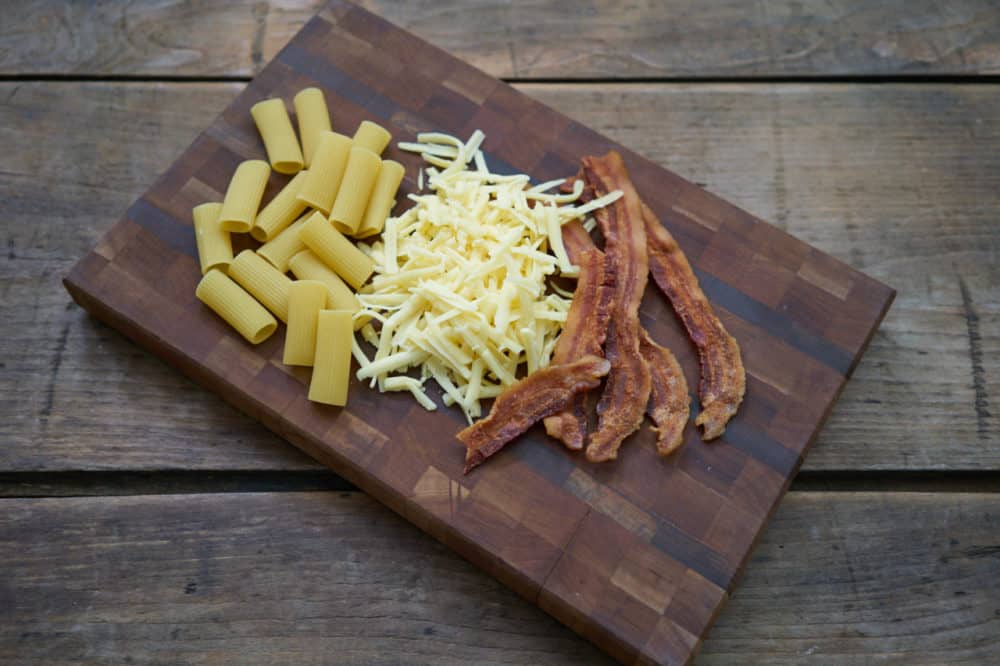 A wooden cutting board with ingredients for creamy pasta with bacon and comté cheese sits on a wooden table. Bacon, shredded cheese, and dried rigatoni noodles are on the cutting board.