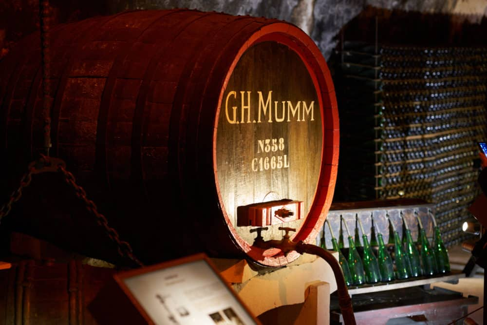 An old Champagne aging barrel on display at G.H. Mumm in Reims, France. The barrel is trimmed in red paint and says, G.H. Mumm in yellow lettering along with some serial numbers. Green bottles are seen on the right.