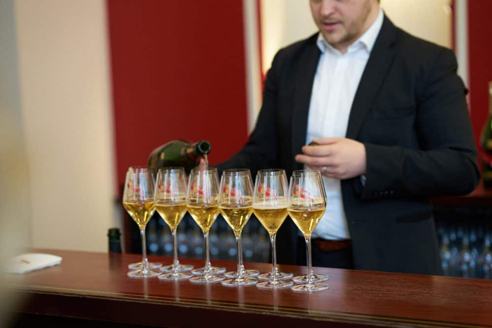 A tour guide at G.H. Mumm in Reims, France pours glasses of Champagne for visitors to taste. 6 glasses of Champagne are lined up on a wooden bar, with a red wall in the background.