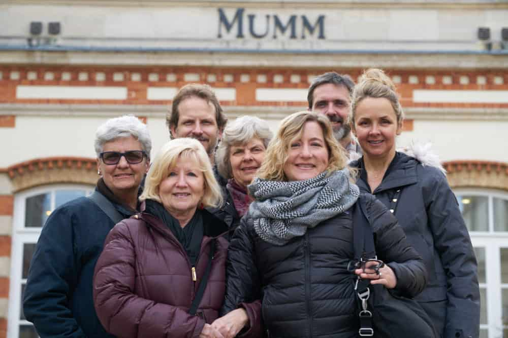 A family of seven adults wearing winter coats are smiling for a portrait in front of G.H. Mumm in Reims, France. There are two men and five women.