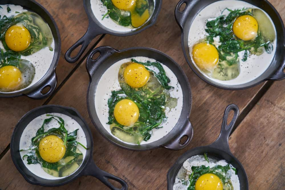 Several small cast-iron skillets and serving dishes containing a small amount of cooked spinach, raw eggs, and some heavy cream are displayed on a wooden surface.