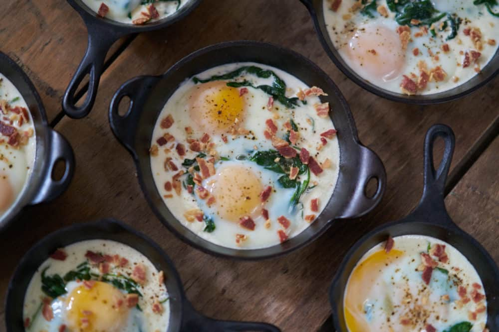 Several servings of eggs en cocotte with spinach and bacon in small cast-iron skillets and serving dishes are displayed on a wooden surface.