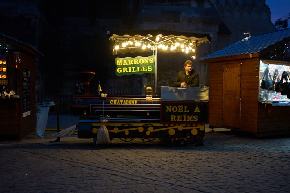 A roasted chestnut cart at the Christmas market at Reims cathedral in France. The cart is decorated like a steam train engine in green and yellow. Signs say Marrons grilles, Noël á Reims.