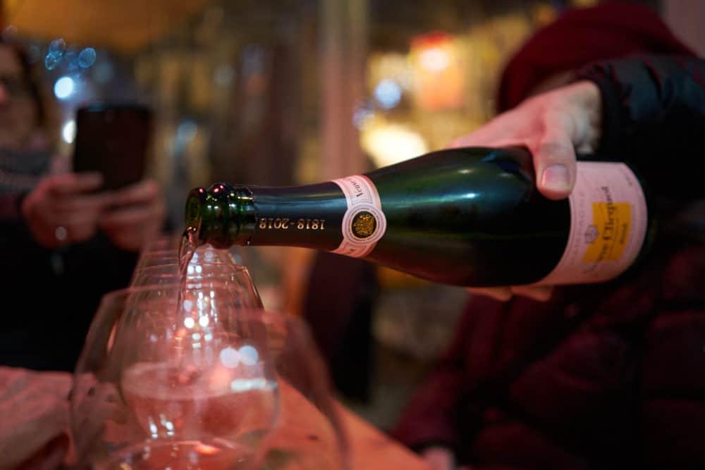 A man pours a bottle of Veuve Cliquot rosé champagne into glasses sitting on a wooden table.