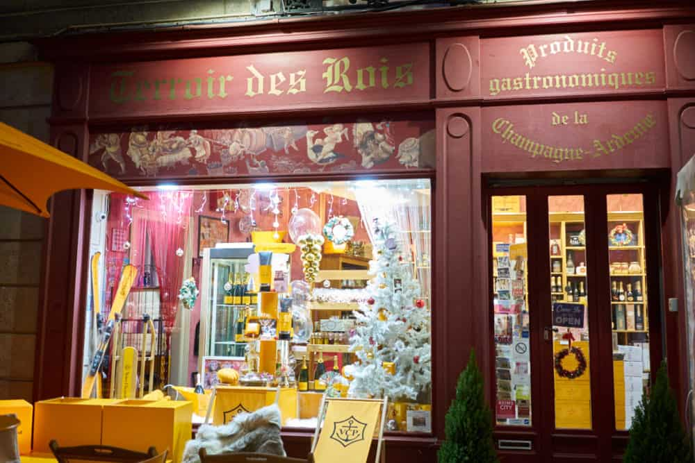 A storefront in Reims, France. It is painted a deep red with gold lettering, it's decorated for Christmas and has Veuve Cliquot window displays. A lounge area advertising Veuve Cliquot champagne is in front of the store.