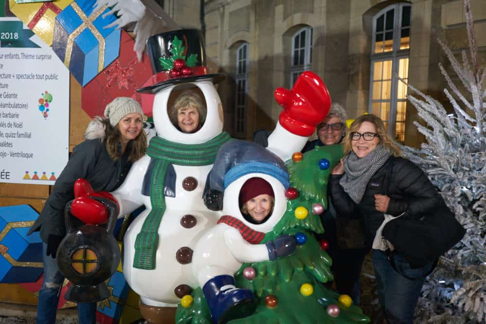 Five women are posing with a Christmas snowman statue at the Christmas market in Reims, France. Two of the women have their faces where the snowman's faces should be. They are all laughing and smiling.