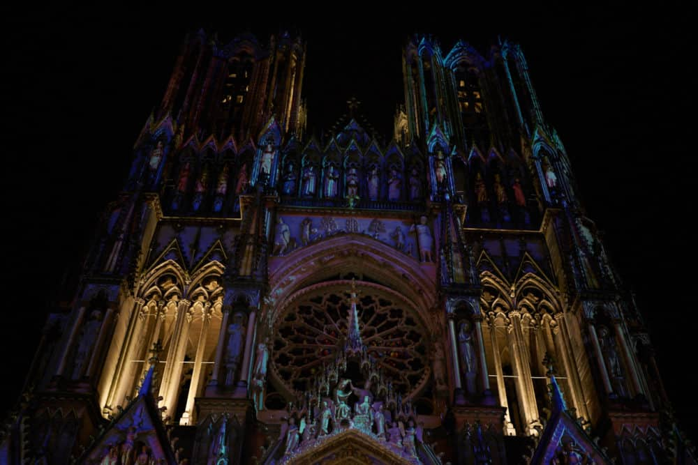 Nighttime view looking up at the front of Reims cathedral during the Christmas market. Blue and purple lights are shining on the gothic stonework.