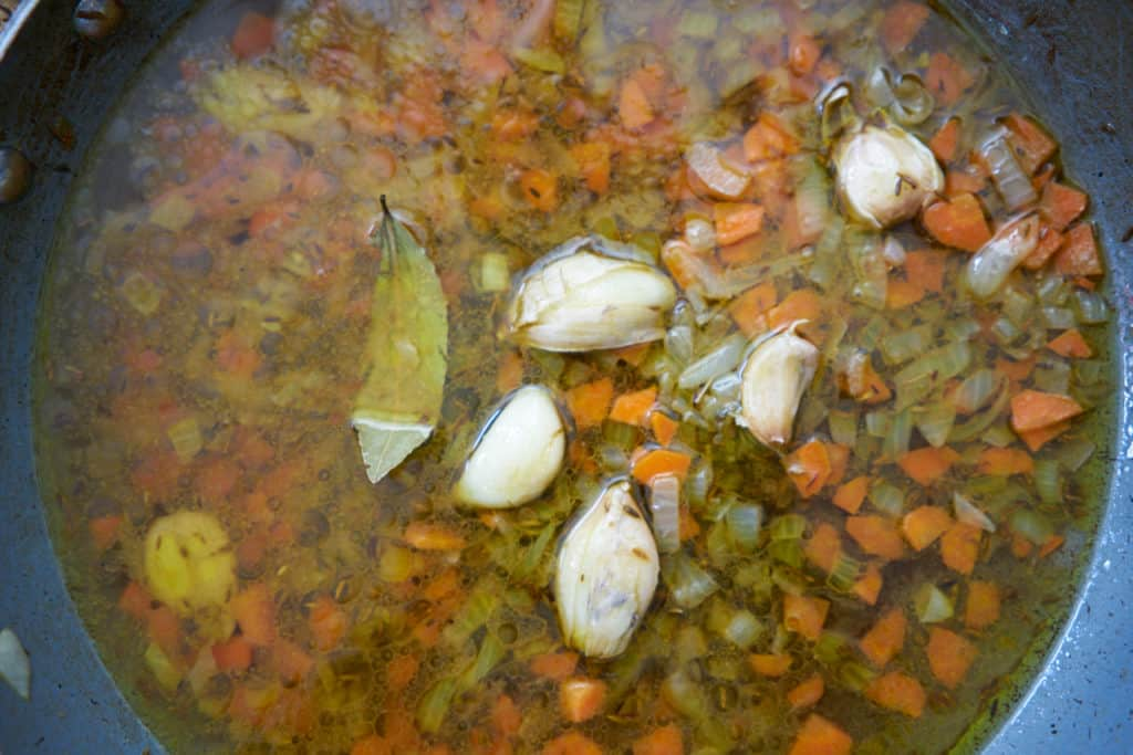 Sauce for chicken escabeche. Chopped onions and carrots can be seen in a clear, vinegar-based broth with whole garlic cloves and a bay leaf.