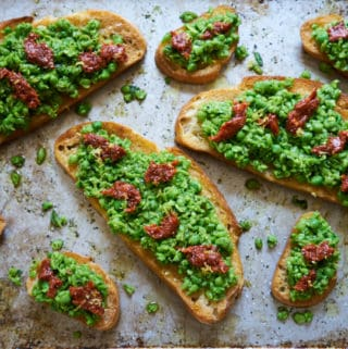 Tartines and crostini with fresh spring peas mixed with mint and lemon and topped with nduja are displayed on a baking sheet.