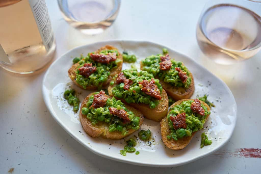 A plate of crostini with peas, mint and nduja along side a wine bottle and two glasses filled with rosé wine.
