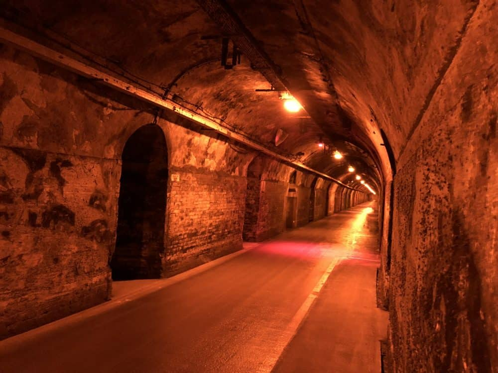 The cellars at G.H. Mumm in Reims, France. A long stone hallway with an arched ceiling is lit with an orange-red light.