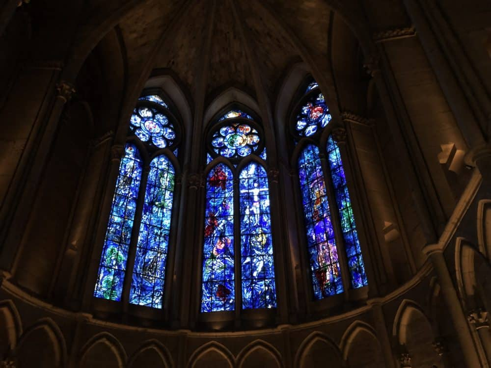 Marc Chagall stained glass windows at Reims cathedral in France. Three narrow window inside a church nave with designs in shades of blue and purple. A praying statue is in the foreground.