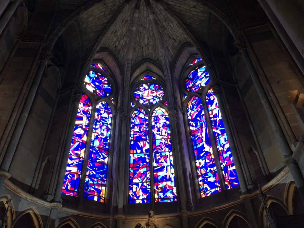 Imi Knoeblel stained glass windows at Reims cathedral in France. Three narrow stained glass windows with a pointed top, the frames are filled with a multi-colored modern stained glass design that looks like confetti.