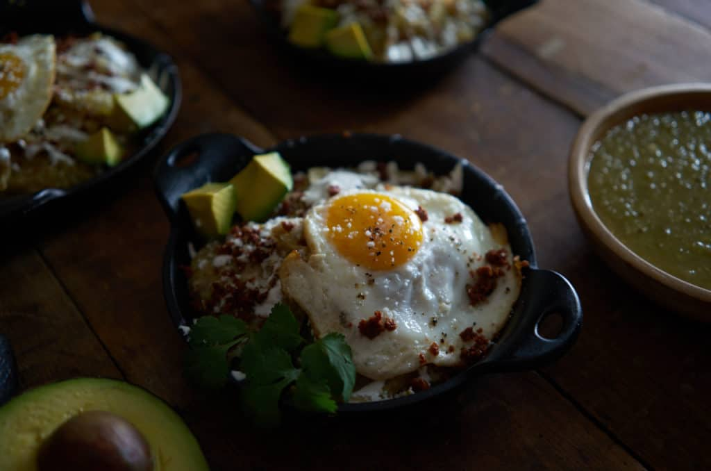 Closeup of a small cast iron dish of chilaquiles verdes topped with a fried egg and chorizo.