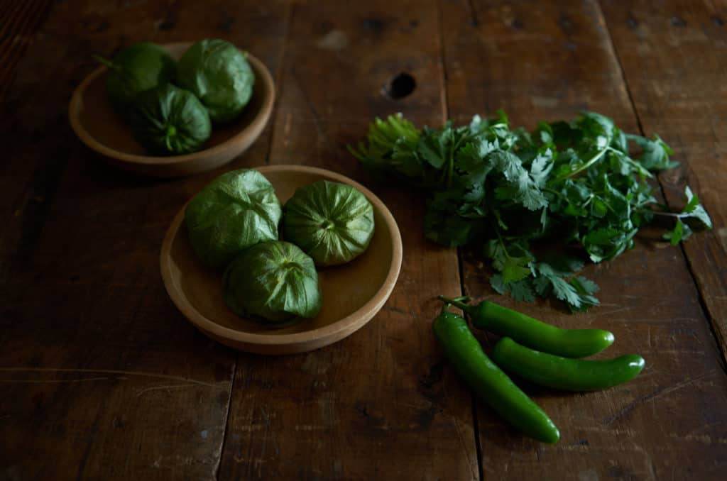 Two small wooden bowls with tomatillos, a bunch of cilantro, and three serrano chiles on a wood surface.