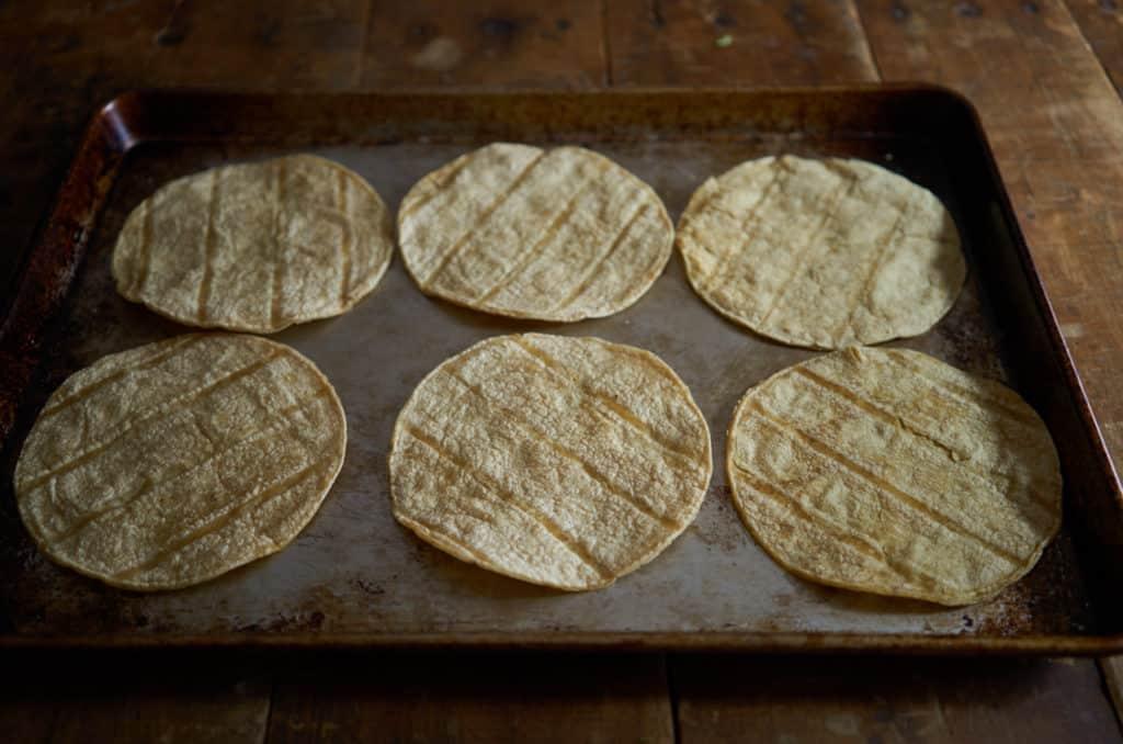Corn tortillas on a baking sheet.