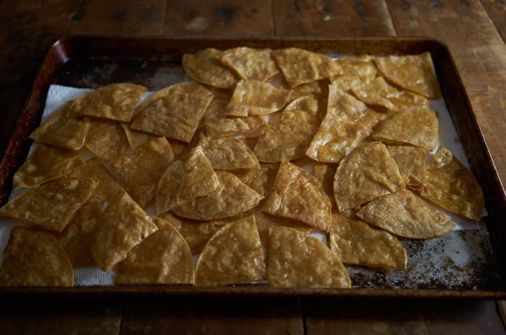 Fried tortilla wedges draining on a paper towel-lined baking sheet.