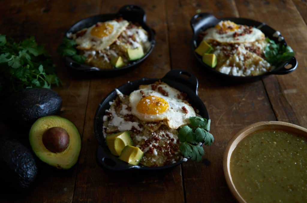 Three small cast iron dishes of chilaquiles verdes topped with a fried egg sit on a wooden table.