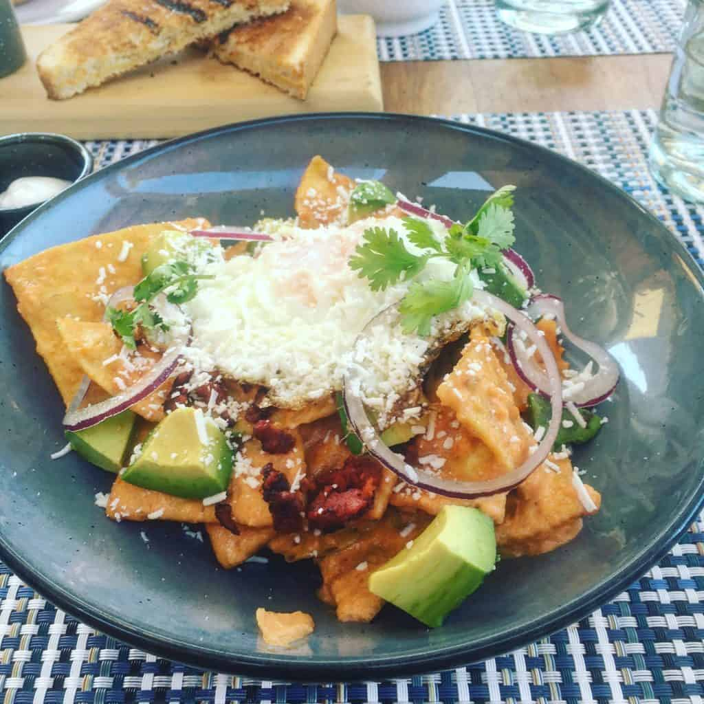 Chilaquiles with fried egg and avocado in a blue bowl at Rancho Pescadero, Baja California Sur.