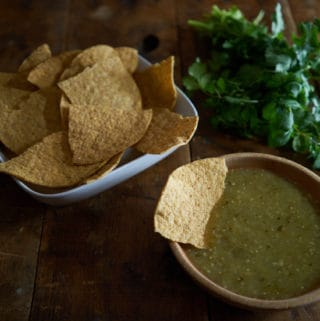 A wooden bowl of salsa verde with a tortilla chip in it, alongside a bowl of tortilla chips and a bunch of fresh cilantro.