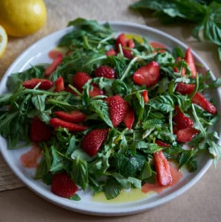 A plate of salad with arugula, herbs, and sliced strawberries on a brown surface with basil leaves and lemons in the background.