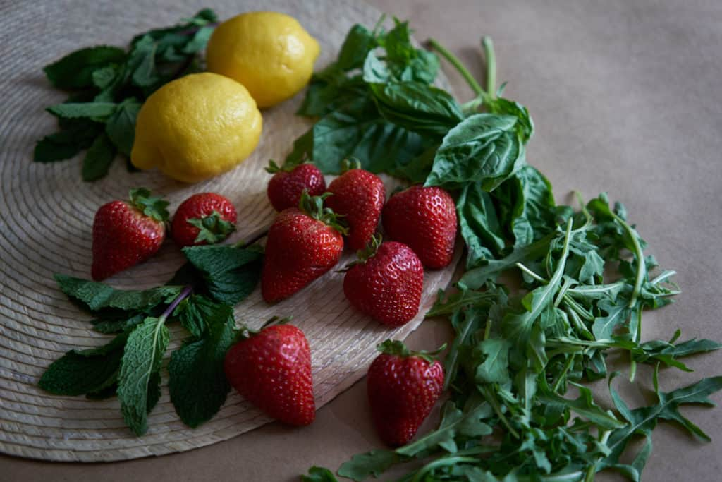 Strawberries, lemons, mint, basil, and arugula on a woven placemat.