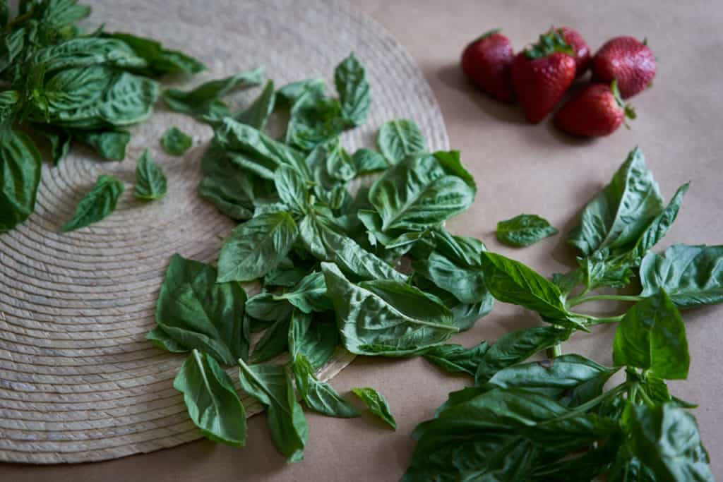 Fresh basil lays on a woven placemat and brown butcher paper. Strawberries are in the background.